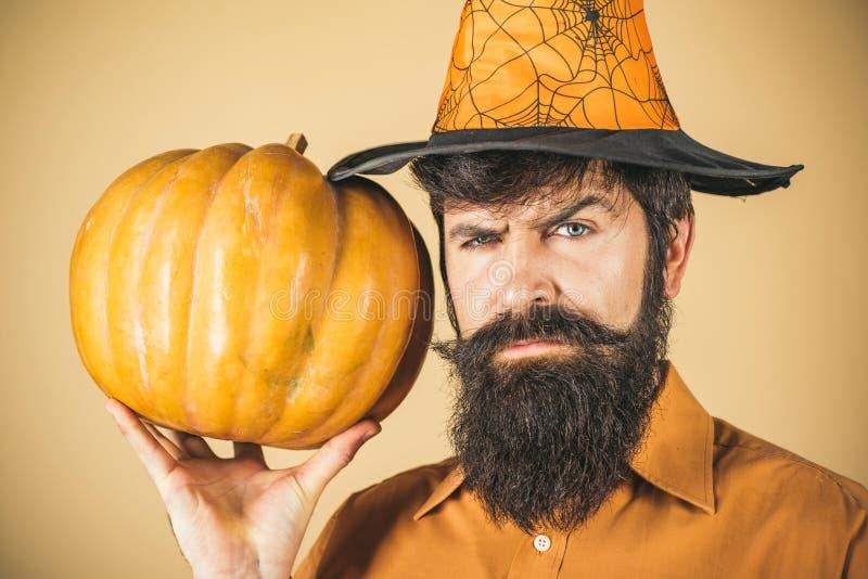 Handsome man in Halloween hat holding pumpkin - portrait close up. Happy Halloween - handsome man . Design for. Halloween banner stock photos