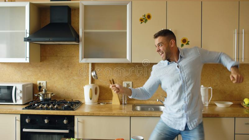 Handsome man having fun in the kitchen fencing with ladle and spoon while cooking breakfast at home royalty free stock photos