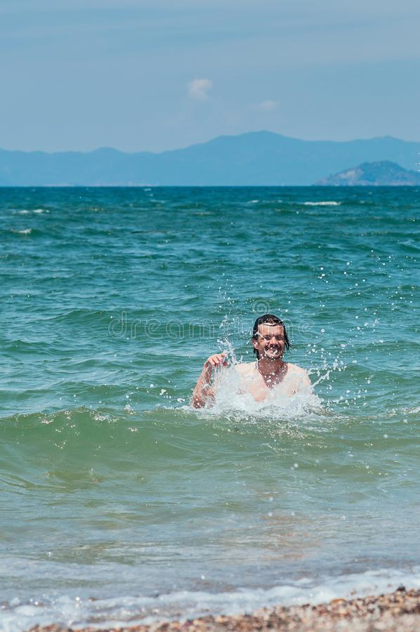 Handsome man having fun in the sea, splashing water. Summer holiday concept royalty free stock images