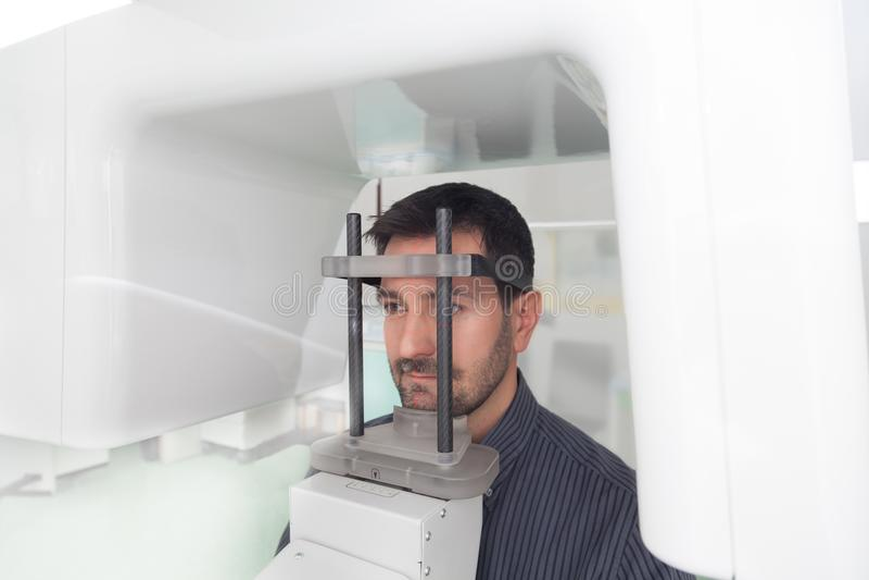 Handsome man having panoramic digital x-ray of his teeth. Handsome man have panoramic digital x-ray of his teeth in a dentalhospital clinic dental stock image