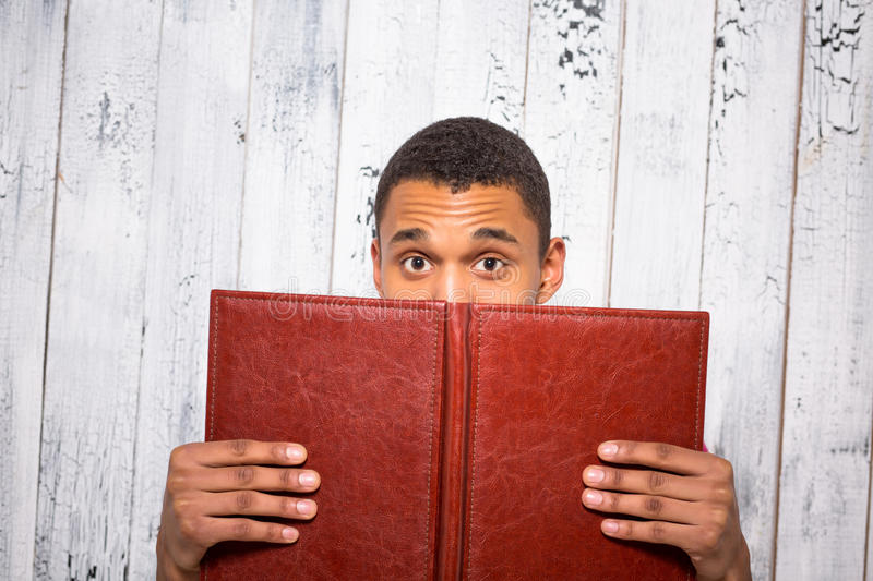 Handsome man hiding behind register or journal in studio royalty free stock photos