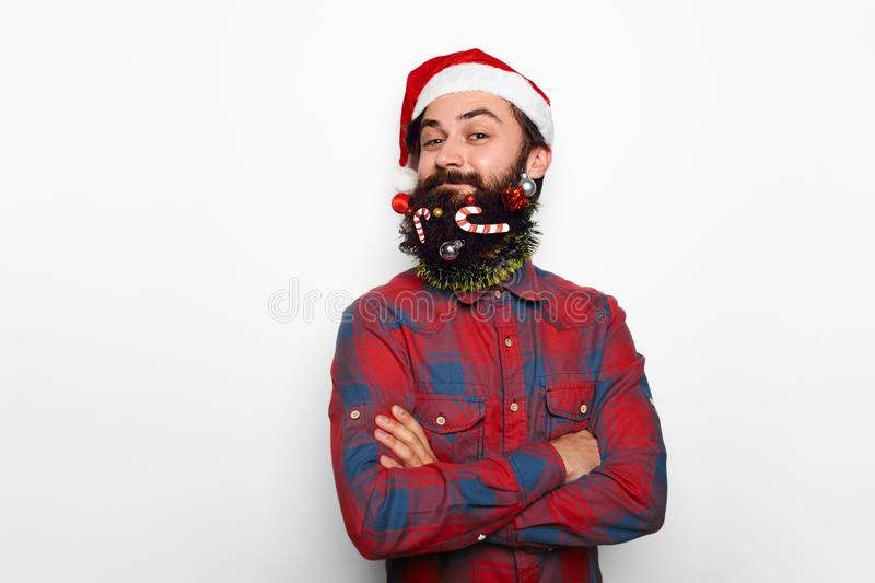 Handsome man hipster male with santa hat over white. Handsome man hipster male with long decorated beard and moustache over white background with copy space stock photo