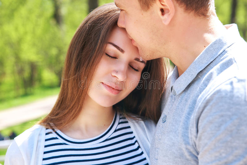 Handsome man and his beautiful pregnant wife are hugging and smiling while standing in park royalty free stock image