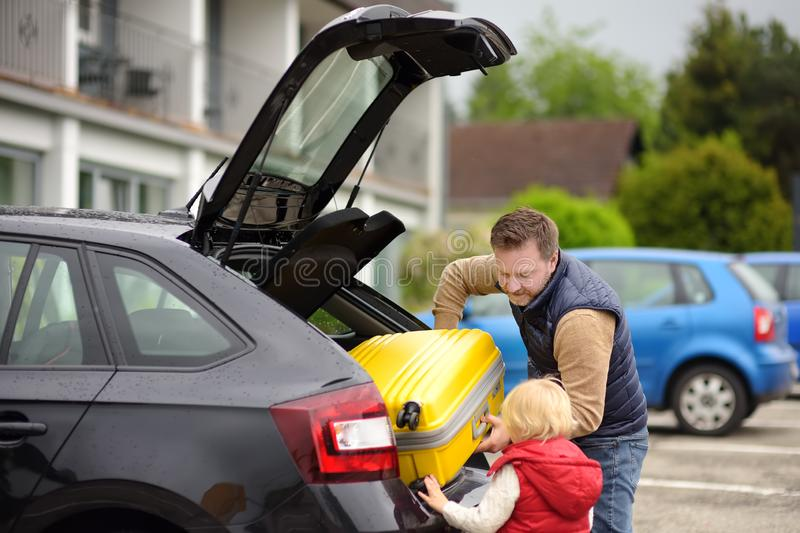 Handsome man and his little son going to vacations, loading their suitcase in car trunk. Automobile trip in the countryside. Handsome men and his little son royalty free stock image