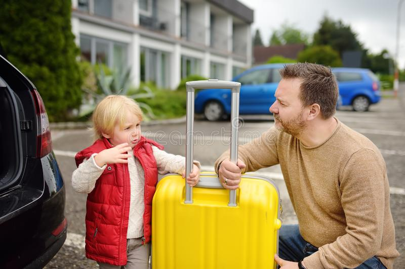 Handsome man and his little son going to vacations, loading their suitcase in car trunk. Automobile trip in the countryside. stock images