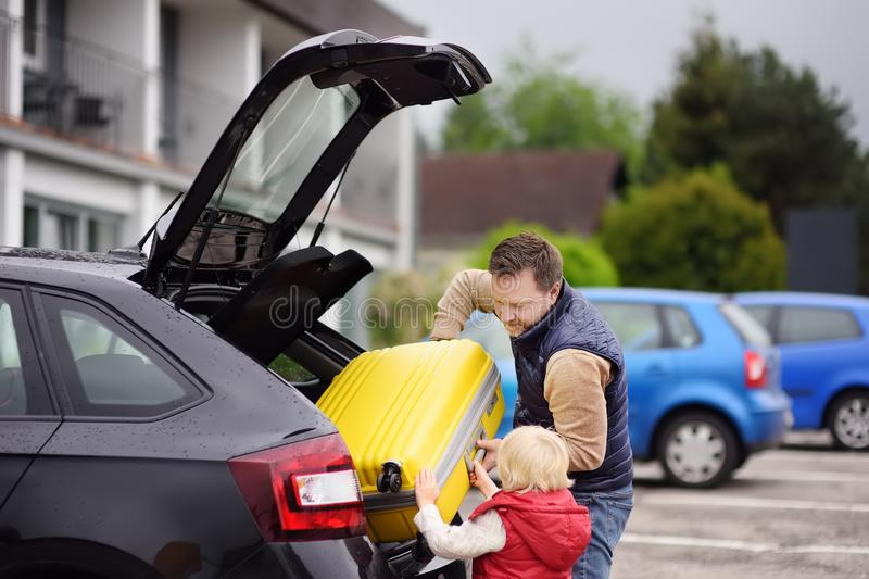 Handsome man and his little son going to vacations, loading their suitcase in car trunk royalty free stock image