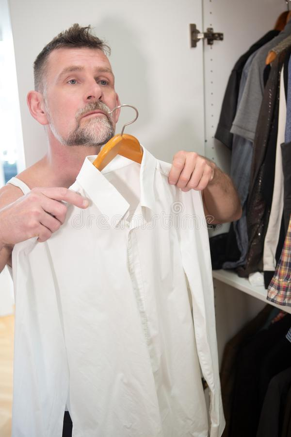 Man in his 50s getting dressed in front of closet. Handsome man in his 50s getting dressed in front of closet royalty free stock photos