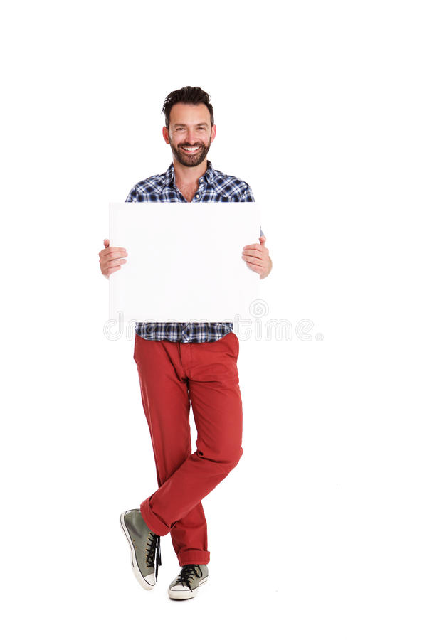 Handsome man holding blank poster over white background. Full length portrait of handsome man holding blank poster over white background royalty free stock photos