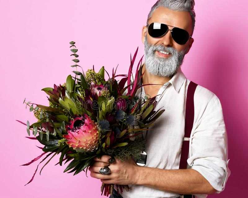 Handsome man holding bouquet of flowers over pink background. Handsome older stylish bearded man in white shirt holding a bouquet of flowers over pink background royalty free stock image