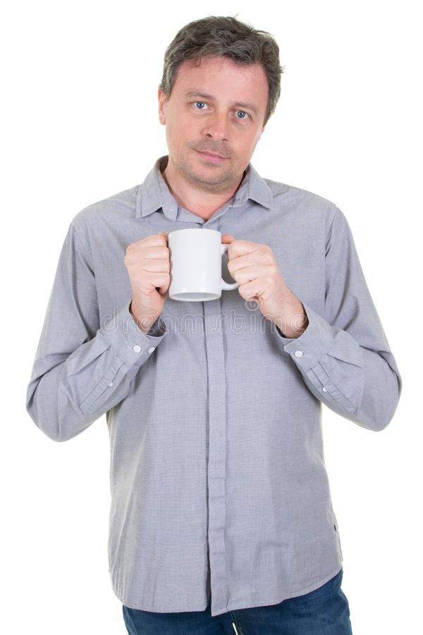 Handsome man holding cup with coffee tea with serious face and blank white mug in hand royalty free stock images