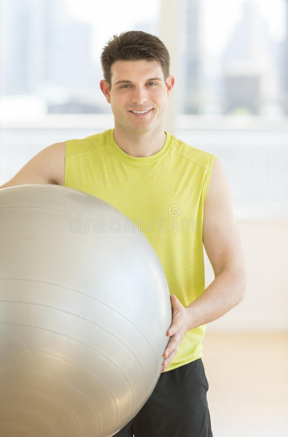 Download Handsome Man Holding Fitness Ball At Gym Stock Photo - Image: 32429880