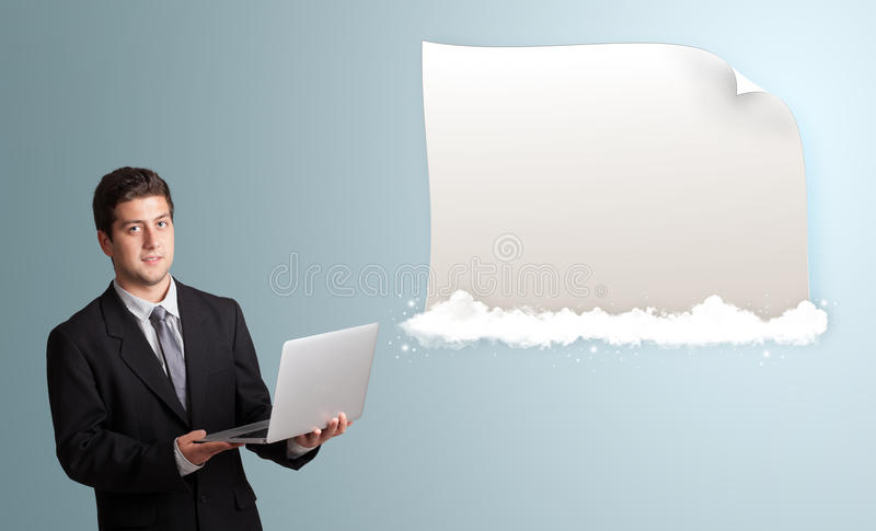 Handsome man holding a laptop and presenting modern copy space o. Handsome young man holding a laptop and presenting modern copy space on clouds stock image