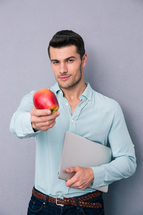 Handsome man holding laptop and showing apple. Over gray background. Looking at camera stock image