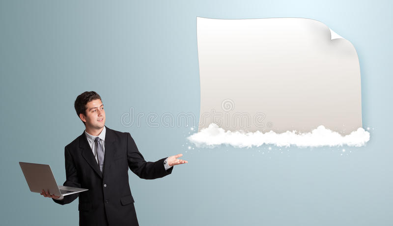 Handsome man holding a laptop. Handsome young man holding a laptop and presenting modern copy space on clouds royalty free stock image