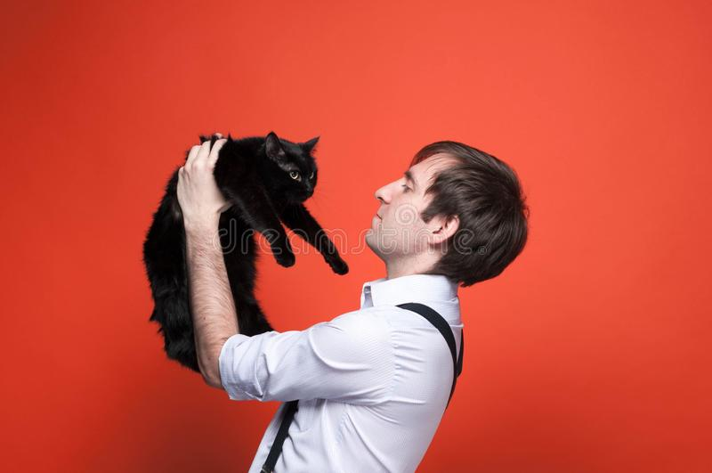 Handsome man holding on outstretched arms and looking at cute black cat. Side view of handsome man holding on outstretched arms and looking at cute black cat on stock photo