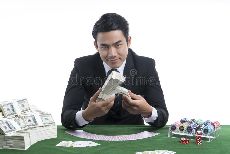 The handsome man holding piles of dollars in hand at casino desk stock images