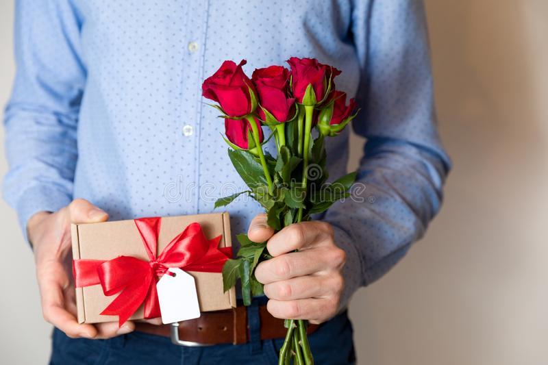Valentines day,man holding red roses and gift with bow and tag,romantic surprise. Handsome man holding red roses and romantic gift with red bow and gift tag,love royalty free stock photo