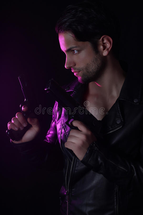 Handsome man holding two guns stock images