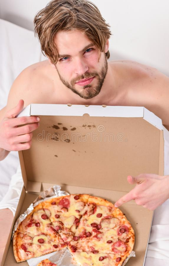 Handsome man holds a piece of pizza in his hands and is about to eat it. Cropped image of shirtless man with pizza stock photo
