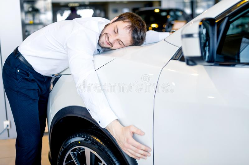 Handsome man hugging his new car in showroom. Emotional happy man hugging his new car in showroom stock image