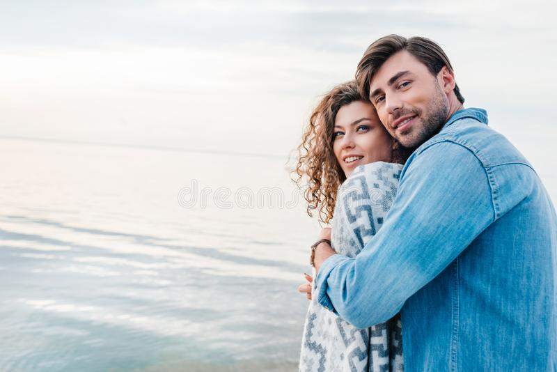 handsome man hugging smiling girlfriend wrapped in blanket stock photos