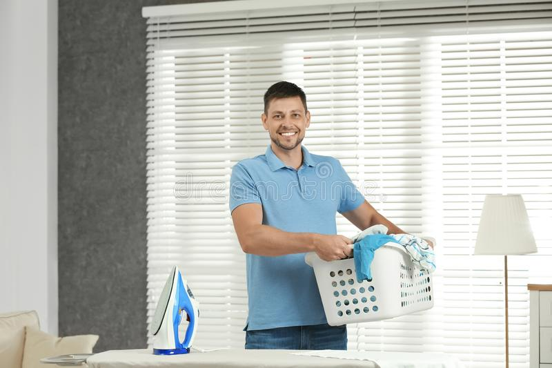 Handsome man with iron and clean laundry near board. At home stock photo