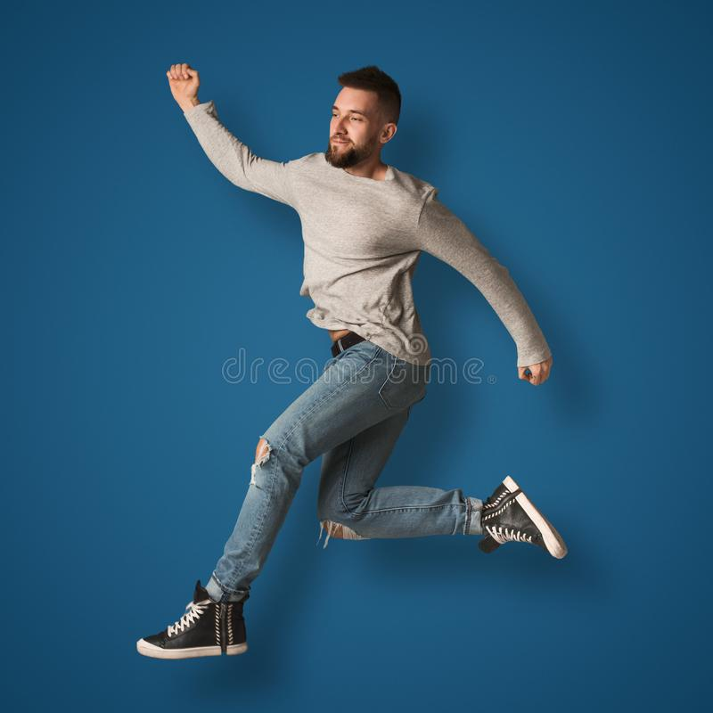 Handsome man jumping in studio royalty free stock photography