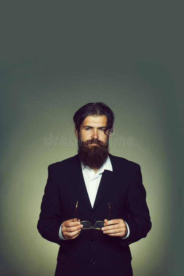 Handsome man keeps glasses. Handsome man bearded hipster male in black suit keeps vintage glasses in hands on grey wall stock photo