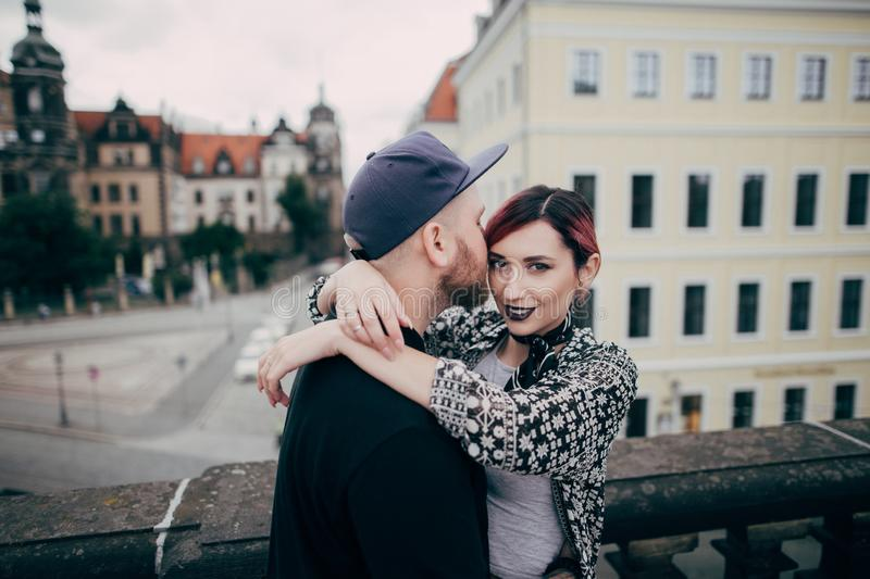 handsome man kissing beautiful young woman looking at camera while standing together on bridge in Dresden stock photos