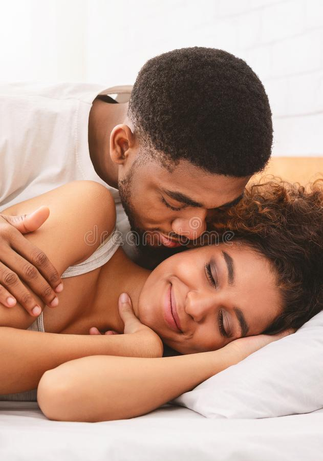 Handsome man kissing woman on cheek under in bed. Good morning, sweetheart. Black men kissing his girlfriend in morning, lying together in bed stock photography