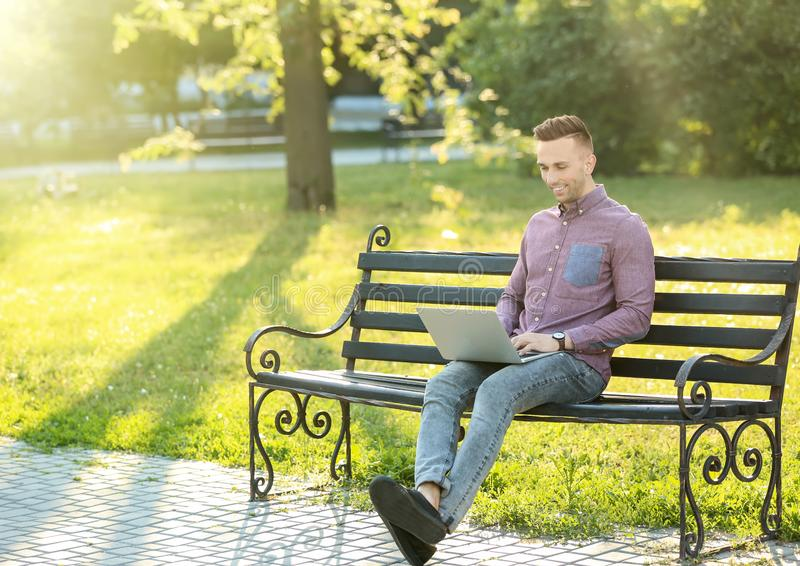 Handsome man with laptop resting on bench in park stock images