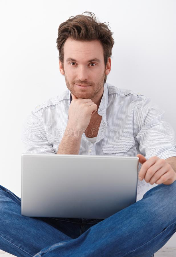 Handsome man with laptop smiling royalty free stock photography