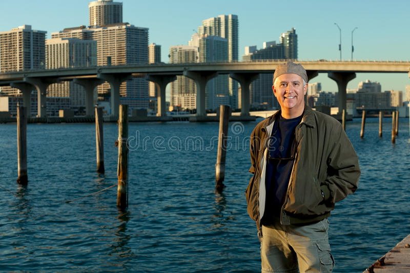 Handsome Man Lifestyle. Handsome man in an urban lifestyle pose wearing a hat with a downtown skyline in the background in the late afternoon at sunset royalty free stock images