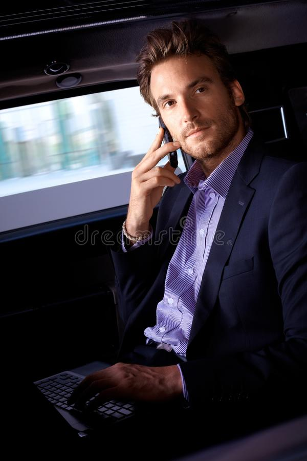 Handsome man in limousine. Handsome young man sitting in limousine, working on laptop computer, talking on mobile royalty free stock photography