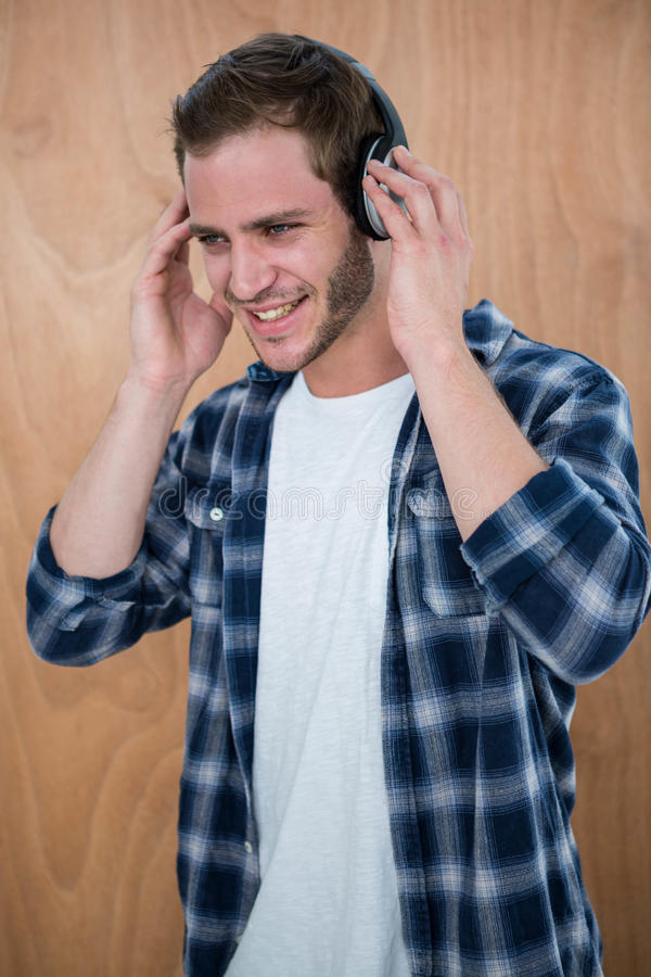 Handsome man listening to music with headphone. On a wooden background stock photography