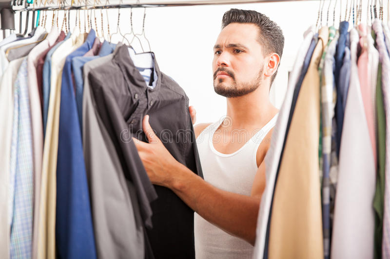 Handsome man looking at his closet. Portrait of an attractive young man with a beard trying to find the right shirt to wear today on his closet stock images