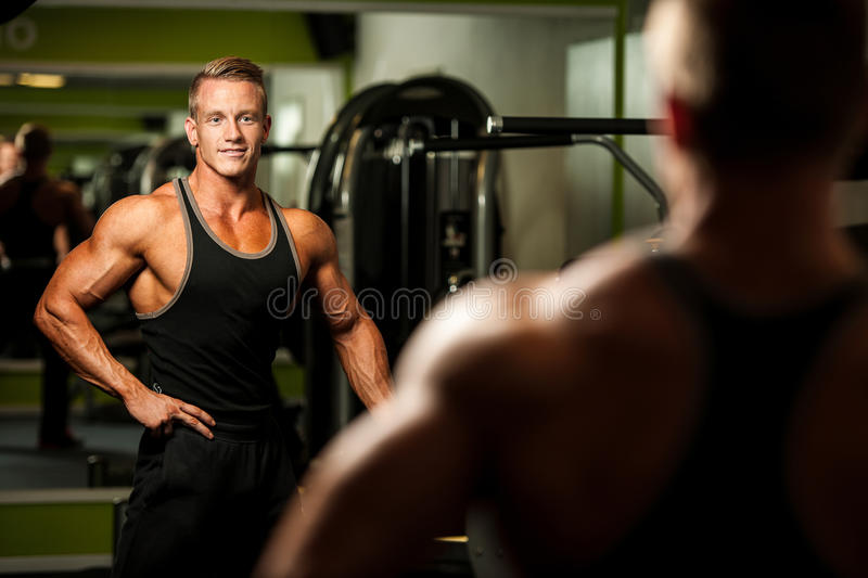 Handsome man looking in mirror after body building workout in fitness stock photo