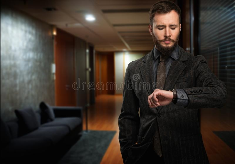 Handsome man looking at wrist watch royalty free stock image