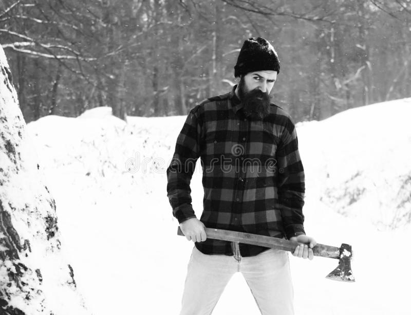 Handsome man or lumberjack, bearded hipster, with beard and moustache in red checkered shirt stands with axe in snowy. Forest on winter day outdoors on natural stock photos