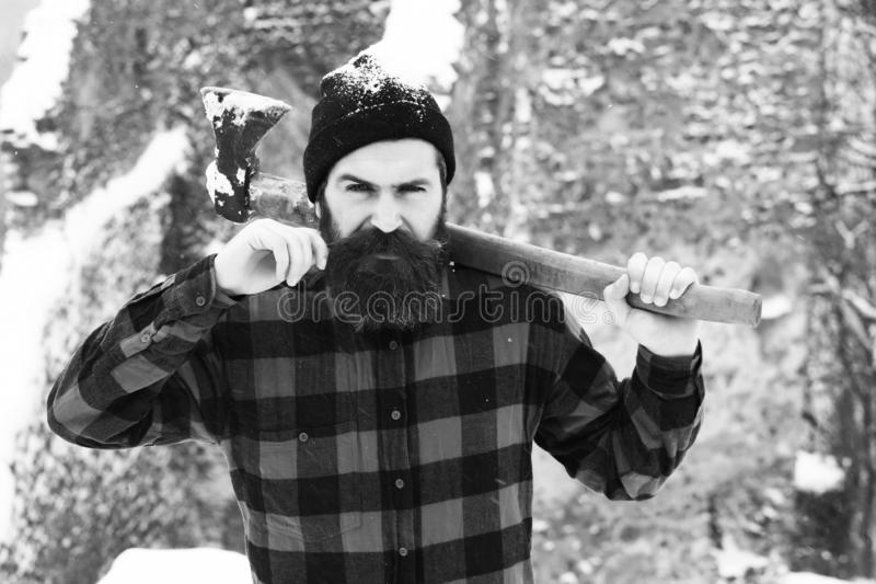 Handsome man or lumberjack, bearded hipster with beard twists moustache in red checkered shirt holding axe in snowy. Forest on winter day outdoors on natural stock image