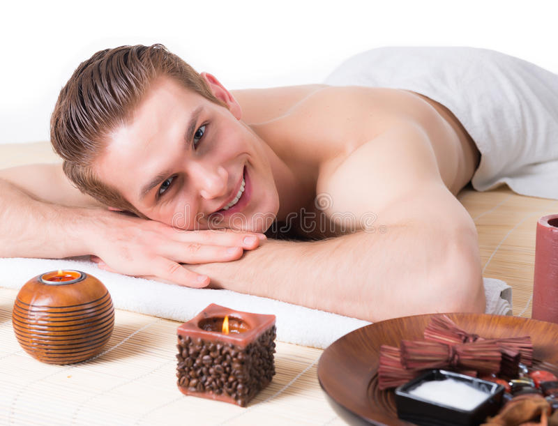 Handsome man lying on the massage desks. Handsome smiling man lying on the massage desks at the spa salon and relax. Beauty treatment concept royalty free stock images