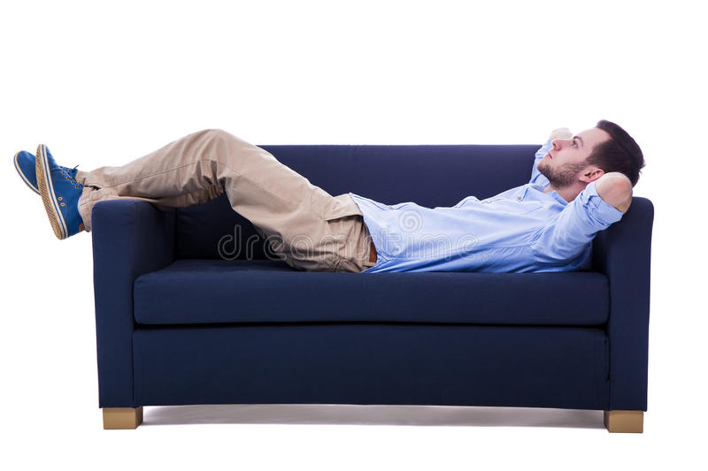 Handsome man lying on sofa isolated on white. Background stock photo