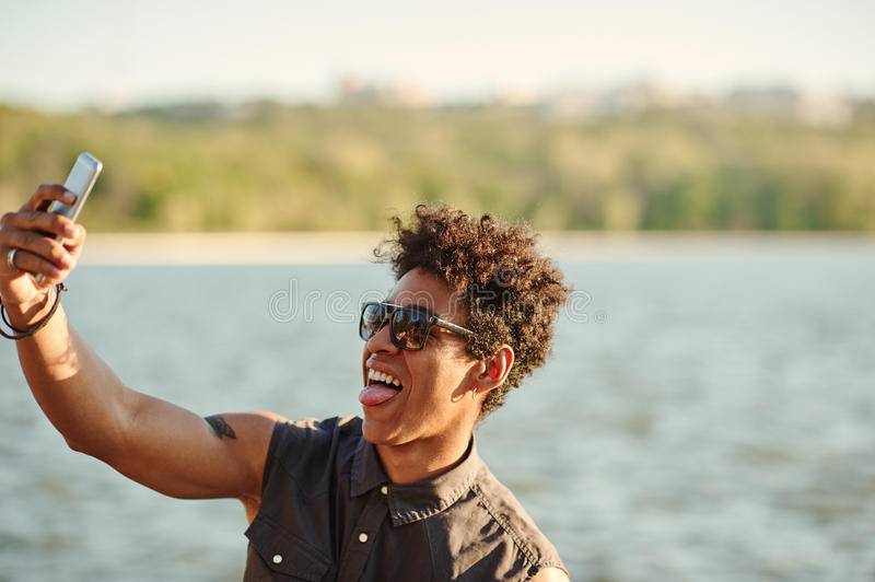 Handsome man making selfie and grimacing with opened mouth. Afro american teenager taking self portrait royalty free stock images