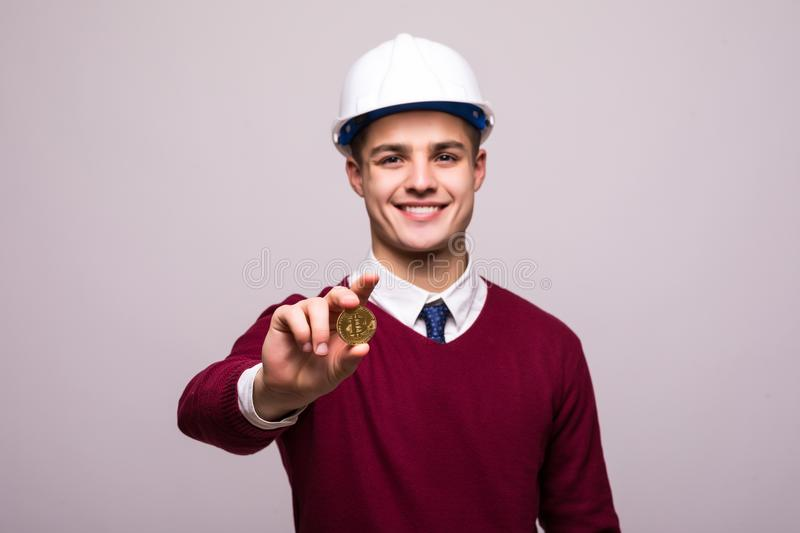 Handsome man miner with protective hamlet holds Bitcoin in his hand. Concept mining crypto currency of Bitcoin royalty free stock photo
