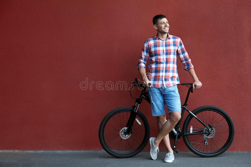 Handsome man with modern bicycle  red wall outdoors stock photography