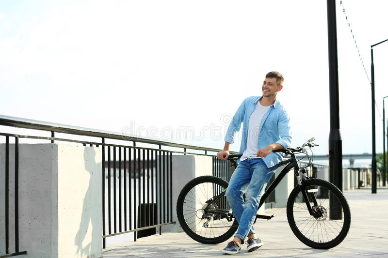 Handsome man with modern bicycle near stock images