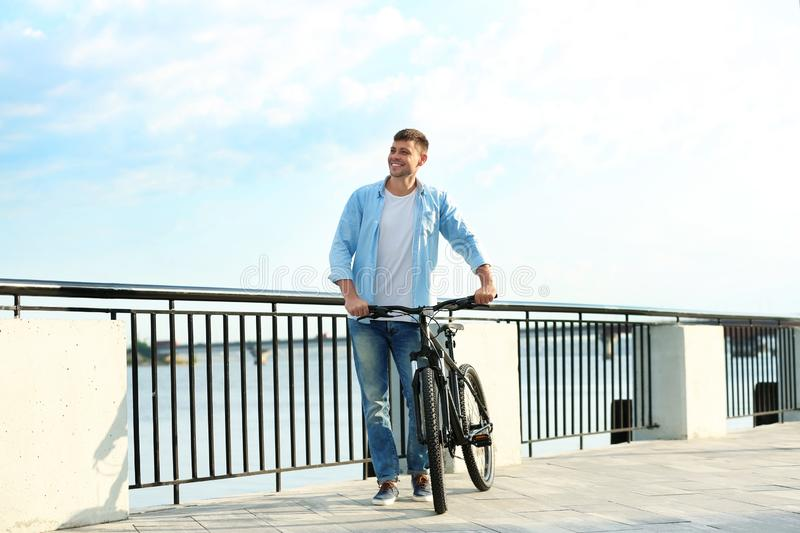 Handsome man with  bicycle near river stock photos