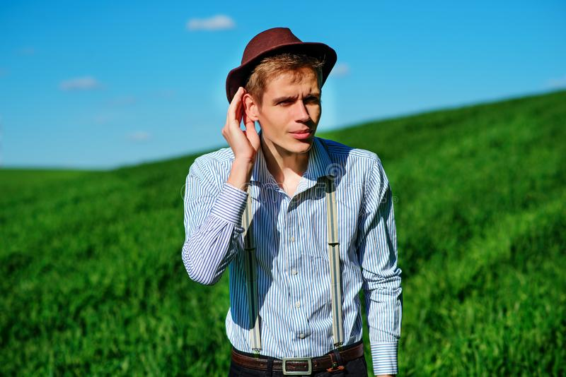 Handsome man in the nature tries to hear something with putting royalty free stock photography