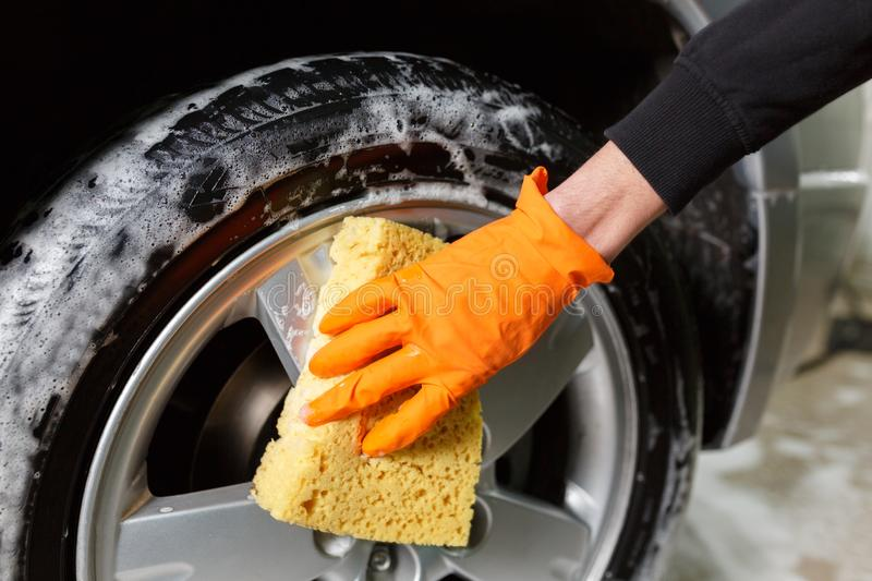 A handsome man washes a tire royalty free stock photography