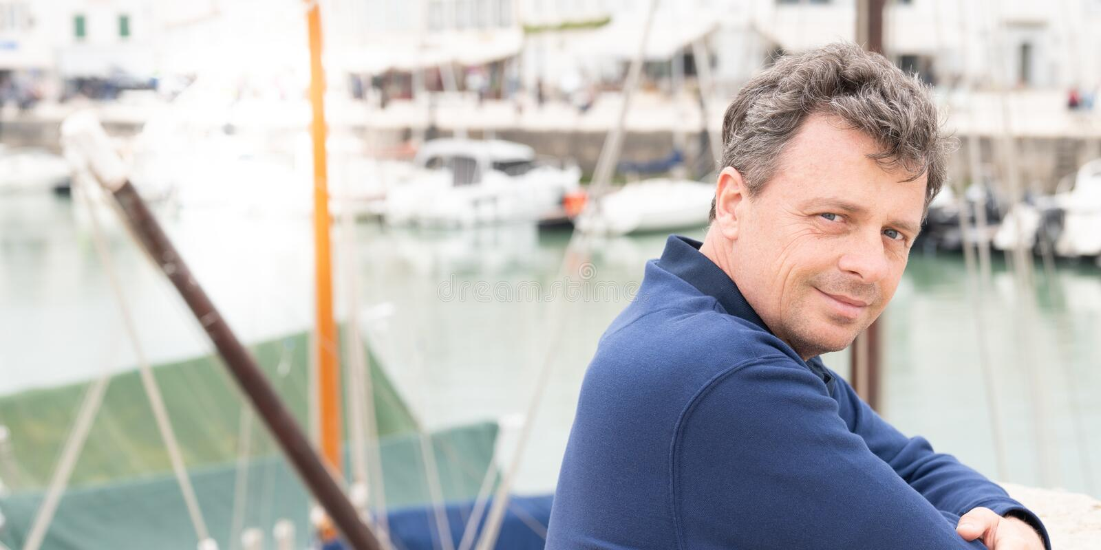 Handsome man outdoor male portrait middle-aged guy posing front sea port in web banner template royalty free stock image